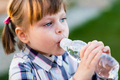 Portrait of little girl drinking water outdoor Royalty Free Stock Image