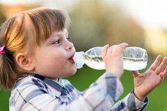 Portrait of little girl drinking water outdoor Royalty Free Stock Photo
