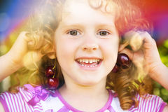 Portrait of a little girl with earrings of cherrys. Royalty Free Stock Photography