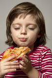 Portrait of little girl eating pizza Stock Photos