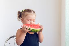 Portrait of a little girl eating a slice of juicy ripe watermelon royalty free stock images