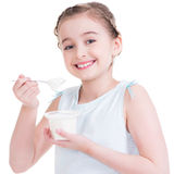 Portrait of a  little girl eating yogurt. Stock Photos