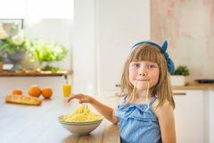 Portrait of a little girl eats a spaghetti and fools Royalty Free Stock Images