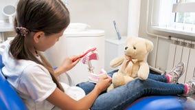 Portrait of little girl educating her teddy bear about teeth hygiene in dentist office. Little girl educating her teddy bear about teeth hygiene in dentist stock photo
