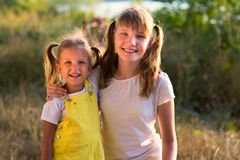 Portrait of a little girl with the elder sister teen in nature stock photography