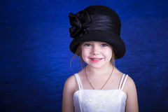 Portrait of a little girl in an elegant hat. On a blue background Stock Images
