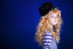 Portrait of a little girl in an elegant hat. Portrait of a little girl in wig and elegant hat on a blue background Royalty Free Stock Photos