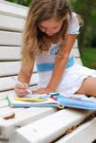 Portrait of the little girl with a fair hair. The little girl with the book and pencils Royalty Free Stock Photos