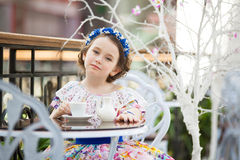 Portrait of little girl in a floral dress drinking tea Royalty Free Stock Photos