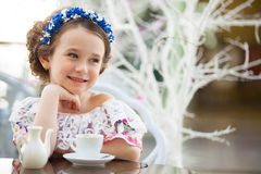 Portrait of little girl in a floral dress drinking tea Stock Photography
