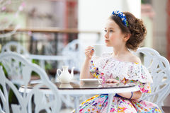 Portrait of little girl in a floral dress drinking tea Stock Photo