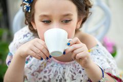 Portrait of little girl in a floral dress drinking tea Royalty Free Stock Images