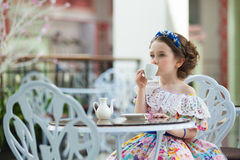 Portrait of little girl in a floral dress drinking tea Stock Photos