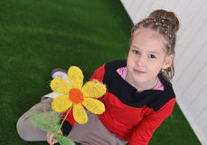 Portrait of a  little girl  with flower sitting on the floor Royalty Free Stock Photos