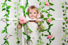 Portrait of a little  girl in flowers. Portrait of a little smiling girl in flowers Stock Image