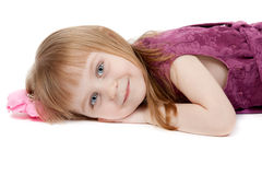 Portrait of a little girl four years old. Beautiful girl aged four years lying on the floor. Isolate on white Royalty Free Stock Photography