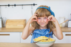 Portrait of a little girl funny eats a spaghetti from a dish and smiling Stock Photos