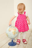 Portrait of little girl with globe in hands, on it. White background.  Horizontal format Royalty Free Stock Photo