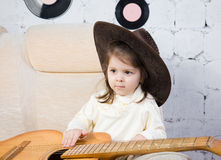 Portrait of the little girl with a guitar in hands Stock Photos