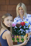 Portrait of a little girl handing over artificial flowers in crate to mother Stock Photos