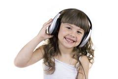 Portrait of the little girl in headphones Stock Photos