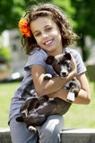 Portrait of little girl with her dog. In garden Royalty Free Stock Image