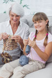 Portrait of a little girl and her granddaughter knitting togethe Stock Photos