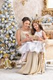 Girl with her mother with Christmas gift. Portrait of little girl with her mother with Christmas gift Royalty Free Stock Photos