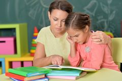 Portrait of little girl with her mother doing homework stock image