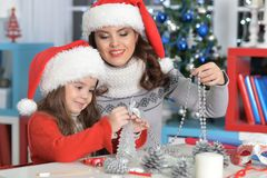 Girl with mother preparing to Christmas. Portrait of little girl with her mother preparing to Christmas Stock Photos