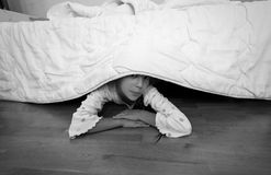 Portrait of little girl hiding under bed at house Royalty Free Stock Photo