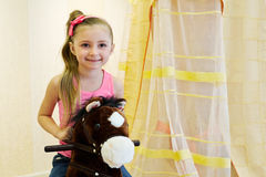Portrait of little girl on hobbyhorse Royalty Free Stock Photography