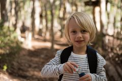 Little girl holding bubble wand in her hand in the forest on a sunny day Royalty Free Stock Images