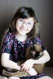 Portrait of little girl holding burmese cat Royalty Free Stock Images