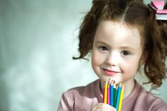 Portrait of little girl holding colored pencils and looking at camera