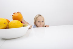 Portrait of little girl holding orange from fruit bowl Royalty Free Stock Photography
