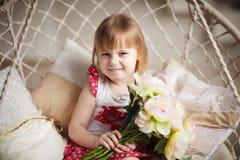 Portrait of little girl holding peonies Stock Photos