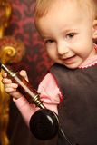 Portrait of little girl holds up retro phone. Interior in retro style. �lose up Royalty Free Stock Photography