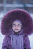 Portrait of a little girl in the hood with fur Stock Photos