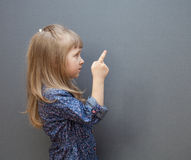 Portrait on a little girl indicating the something. On grey background Royalty Free Stock Images