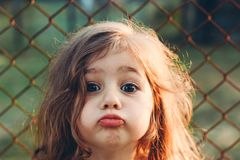 Portrait of cute little Girl with kissing lips looking at camera. Portrait of little Girl with kissing lips looking at camera. Happy Kid outdoors royalty free stock photo