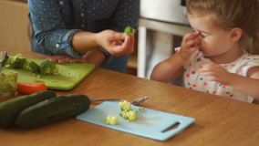 Portrait of a little girl in the kitchen. Mom gives the daughter a broccoli and a carrot. The girl pushes the vegetables stock video footage