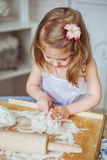 Portrait of a little girl kneads a dough. On a kitchen Stock Photo