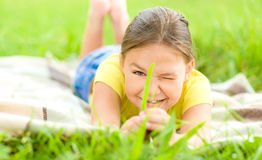 Portrait of a little girl laying on green grass Royalty Free Stock Photo