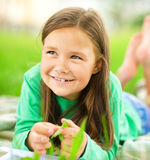 Portrait of a little girl laying on green grass Stock Photos