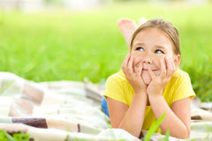 Portrait of a little girl laying on green grass Royalty Free Stock Photography