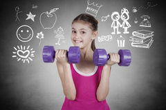 Portrait of a little girl lifting dumbbels Royalty Free Stock Image