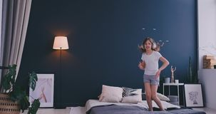 Portrait of a little girl listening to the music with the headphones and dancing on her parents bed. Concept: Music stock footage