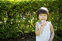 Portrait of a little girl with lollipop. In the park Stock Images