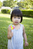 Portrait of a little girl with lollipop. In the park Stock Photo